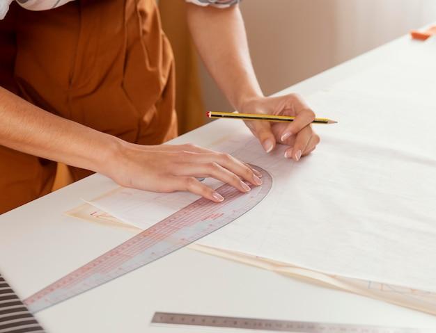 Mani del primo piano con righello e matita
