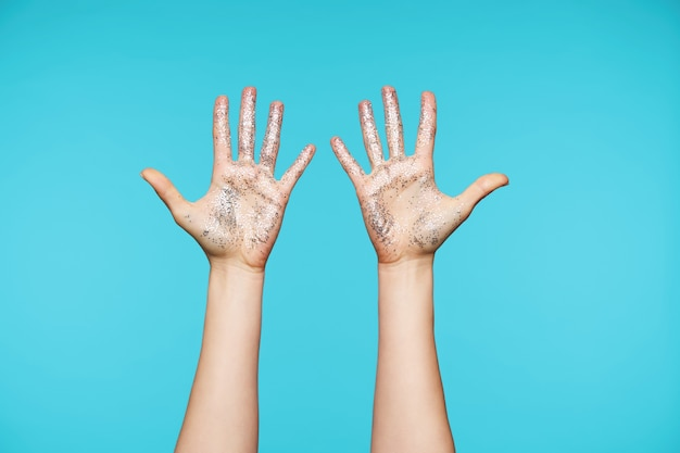 Close up on hands with silver sparkles keeping all fingers separately while showing palms