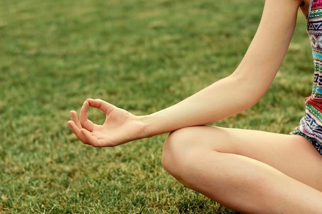 手を閉じます。女性は屋外でヨガを行います。フィットネスライフスタイルクラブのバイタルと瞑想を行使する女性