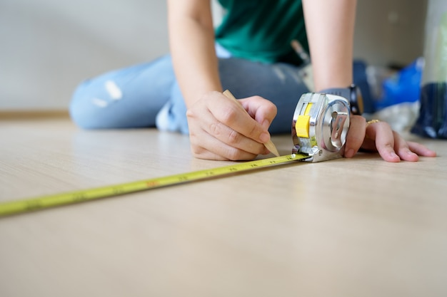 Close up hands woman engineer with yellow carpenters tape