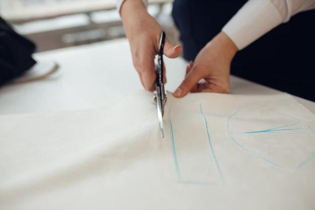 Закройте вверх. руки женщина портной работает, кроет рулон ткани, на котором она мелом разметила выкройку одежды, которую шьет.