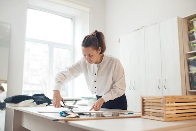 확대. hands woman 재단사 분필로 그녀가 만들고있는 의복 패턴을 표시 한 직물 롤 절단 작업.
