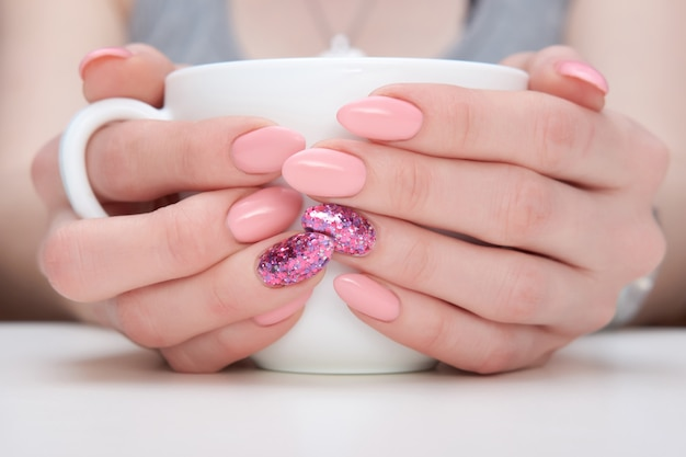 Close up hands of woman with pink manicure holding cup of coffee or tea.