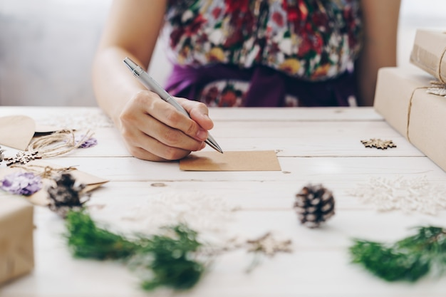 Close up of hands woman writing empty wishlist and christmas card on wooden table with xmas decoration.