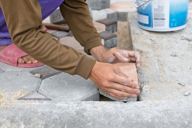 Close-up of hands of worker working on placing stone block for foot path. construction work concept.
