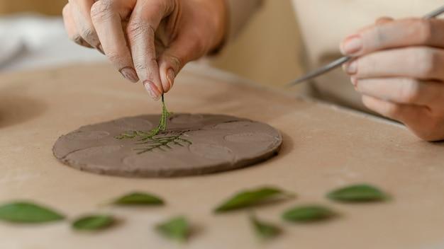 Mani del primo piano che lavorano con pianta e argilla