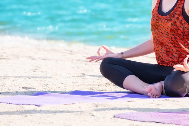 Close up hands of yoga group seated doing hand mudra and meditates on sand at coastline beach