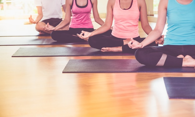 Close up hands of yoga group seated doing hand mudra and meditates in a training studio fitness room