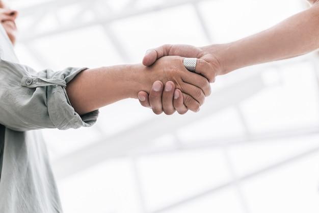 閉じる。ぼやけたオフィスの背景に握手ビジネスパートナー。協力の概念