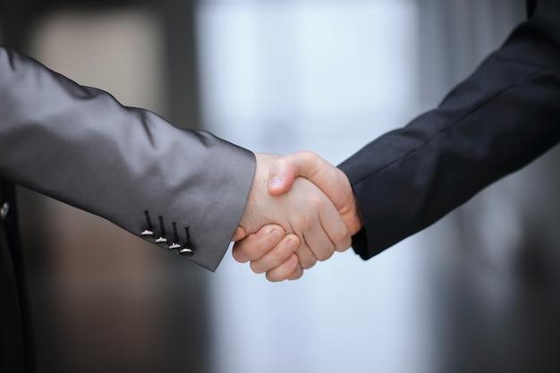 Крупным планом. рукопожатие деловых партнеров на фоне офиса. концепция партнерства