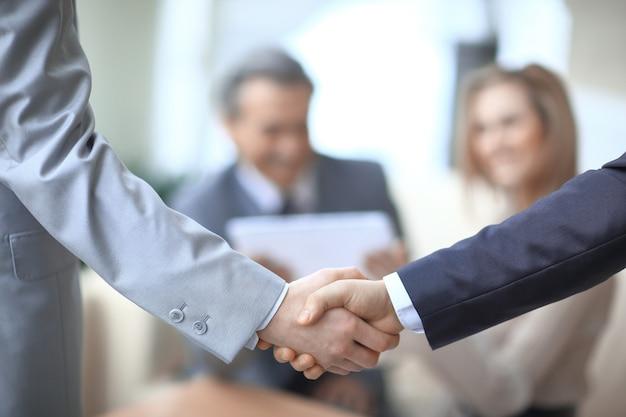 職場の背景にあるビジネスパートナーのクローズアップ握手。