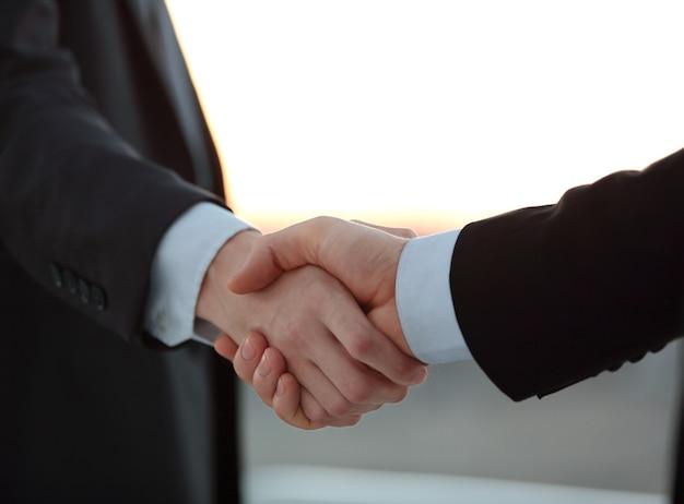 Крупным планом. рукопожатие деловых людей в размытом фоне. концепция сотрудничества