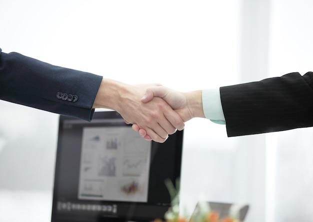 クローズアップ。デスクトップの壁に金融パートナーの握手。パートナーシップの概念