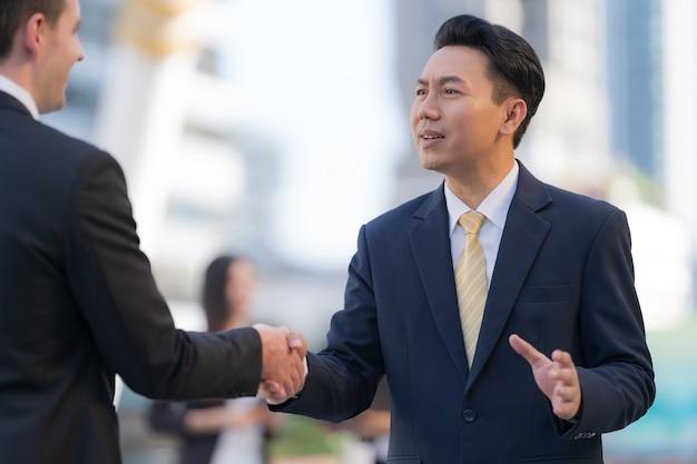 Крупным планом, рукопожатие двух бизнесменов на фоне современного офиса, концепция партнерства