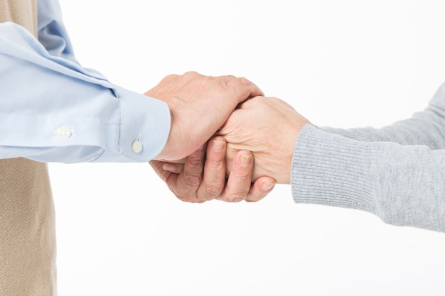 A close up of the handshake between olderly couples