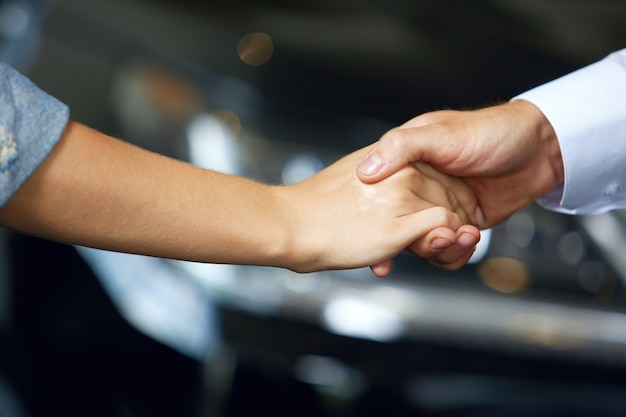 Close-up of handshakes of people who have made a deal to buy a new car