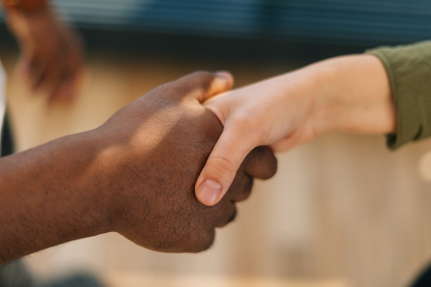 Close-up handshaking of two caucasian business men colleagues on background of window in sunny day. closeup low-angle view of unrecognizable employer hire vacancy candidate shakes hands