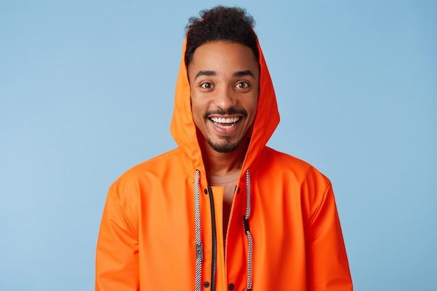 Primo piano di bel ragazzo dalla pelle scura afroamericano indossa in cappotto di pioggia arancione, si sente felice, sorride ampiamente e si alza.