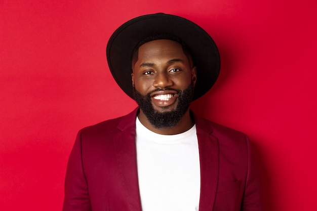 Close-up of handsome african american man with beard, wearing party blazer and stylish hat, smiling at camera, red background