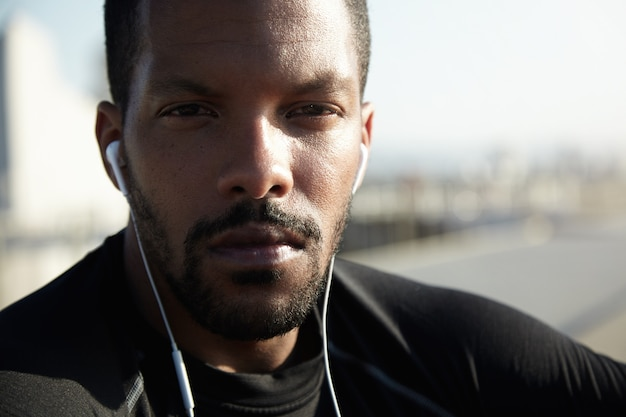 Close up of handsome african athlete with healthy tanned skin and confident look, wearing black sportswear, squinting his eyes while resting outdoors, listening to his favourite music with earphones