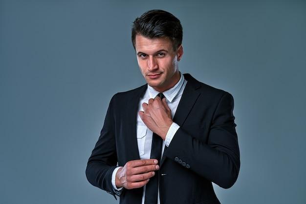 비싼 양복을 입은 잘 생기고 성공한 남자. 그는 넥타이가 달린 흰색 셔츠를 입고 있습니다. 남자는 회색 배경에 대해 넥타이를 곧게 만듭니다.