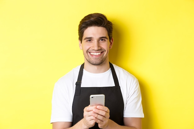 Close-up of handsome barista sending message on mobile phone, smiling happy, standing over yellow background