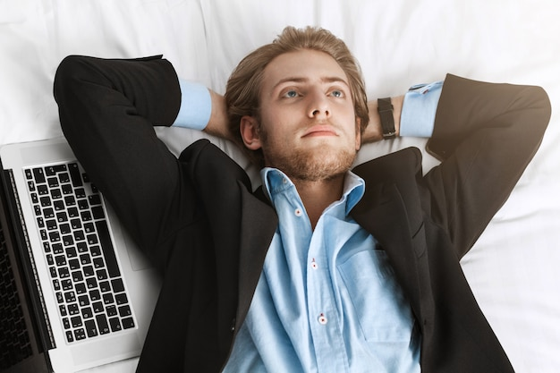 Close up of handsome bearded businessman in fashionable suit lying on back with hands under head with laptop near him, looking upside, thinking about tomorrow's meeting.