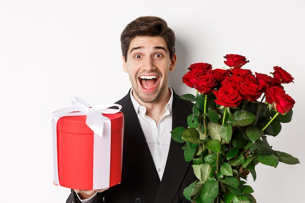 Close-up of handsome bearded man in suit, holding present and bouquet of red roses, smiling at camera, standing against white background