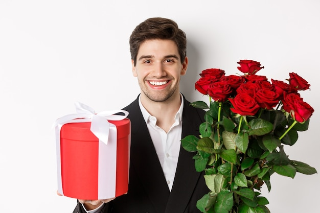 Close-up of handsome bearded man in suit, holding present and bouquet of red roses, smiling at camera, standing against white background.