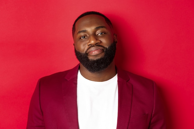 Close-up of handsome bearded plump guy smiling at camera shy, standing in stylish blazer on t-shirt, standing over red background