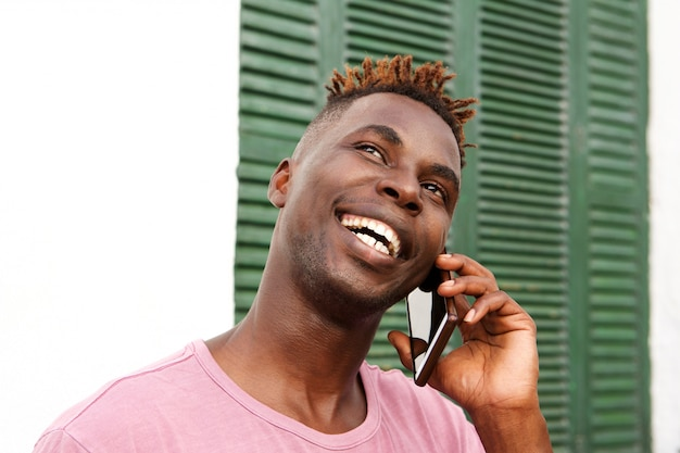 Close up handsome black guy standing outside and talking on mobile phone
