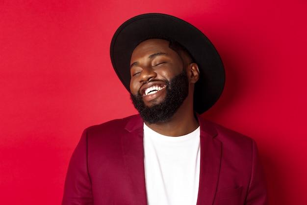 Primo piano di un bell'uomo di colore con la barba lunga che ride e si diverte, sembra spensierato, in piedi su sfondo rosso