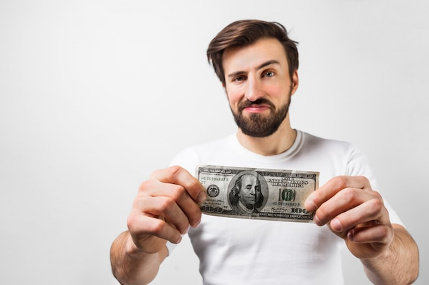 Close up of handsome brunette man standing near the white wall and holding a dollar bill. he is showing that he has one hundred dollar bill. guy looks happy. cut view. isolated on white wall.