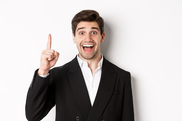 Primo piano di un bell'uomo d'affari in abito nero, sorridente stupito, che mostra il numero uno, in piedi su sfondo bianco