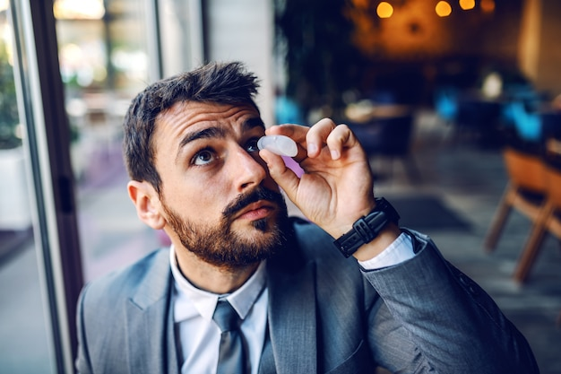 Close up of handsome caucasian elegant businessman in suit sitting in cafe and putting eye drops in eye.