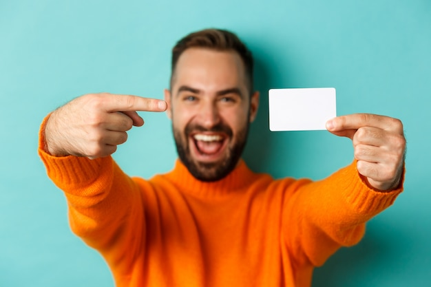 Close-up of handsome caucasian man going on shopping, showing credit card and smiling, standing over turquoise background.