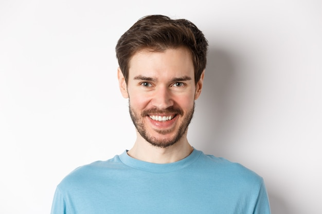 Close-up of handsome caucasian man smiling with white teeth, looking confident at camera, standing in blue shirt on white background.