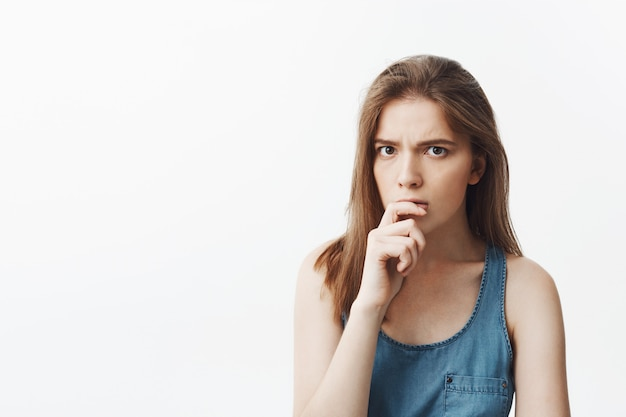 Close up of handsome charming young european woman with long dark hair in casual blue clothes holding hand near lips,  with thoughtful face expression trying to remember name of person