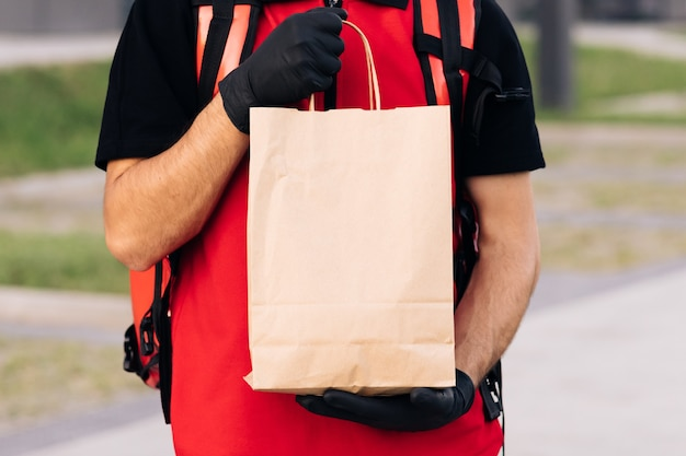 Close up handsome courier man holding paper bag with food at street outdoors worker grocery to house