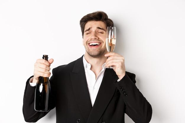 Primo piano di un bel ragazzo ubriaco in tuta, con in mano un bicchiere di champagne e festeggiando il nuovo anno, in piedi su sfondo bianco