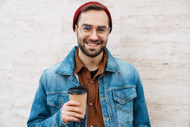 Close up of a handsome happy young stylish bearded man walking outdoors in the street, holding takeaway coffee cup