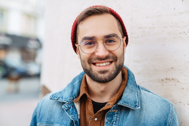 Close up of a handsome happy young stylish bearded man walking outdoors in the street