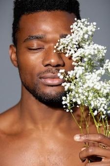 Uomo bello del primo piano che posa con i fiori