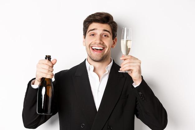 Primo piano di un bell'uomo in tuta, con in mano una bottiglia e un bicchiere di champagne, che celebra le vacanze, in piedi su sfondo bianco