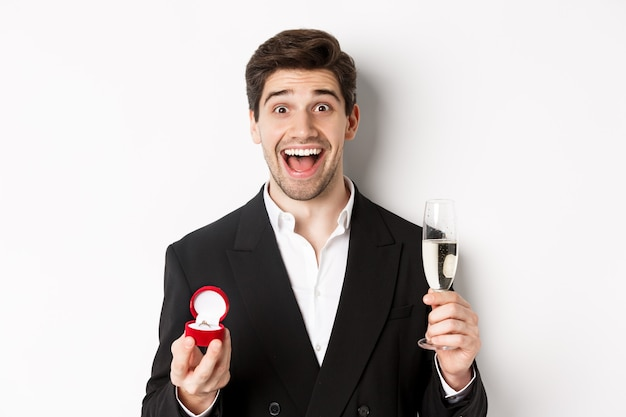 Close-up of handsome man in suit, making a proposal, giving engagement ring and raising glass of champagne, standing against white background