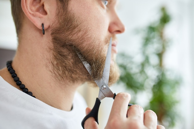Close up of handsome man in white t-shirts cutting beard, moustache personally himself with scissors at home.