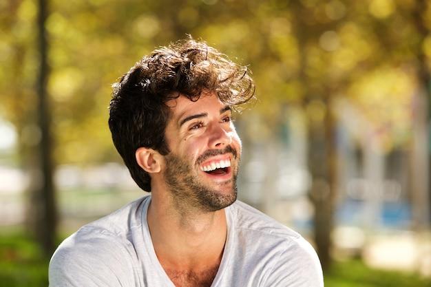 屋外で笑うひげを持つハンサムな男を閉じます