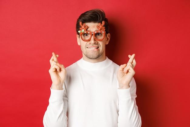 Primo piano di un bel ragazzo nervoso con gli occhiali da festa, esprimere un desiderio, incrociare le dita per buona fortuna e guardare con speranza la telecamera, in piedi su sfondo rosso