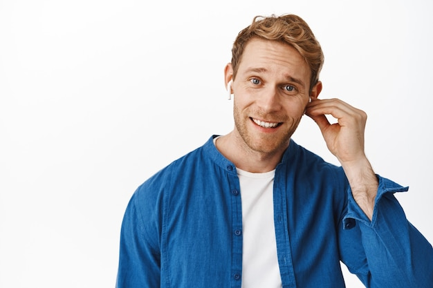Close up of handsome redhead man put on wireless headphone, listening music or talking on mobile phone in earphones, smiling happy at front, standing over white wall