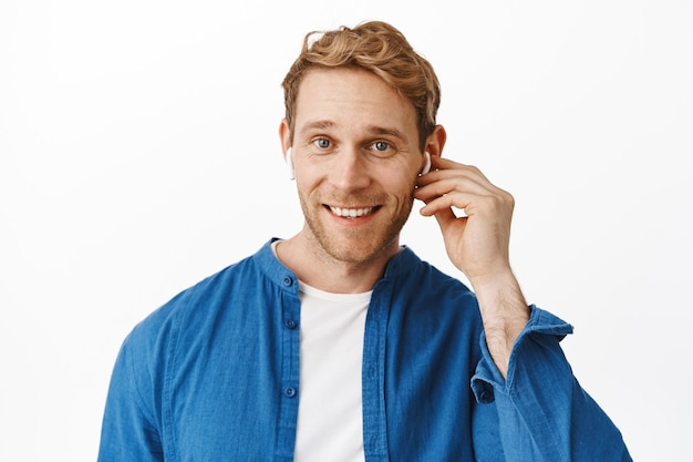Close up of handsome redhead man wears wireless earphone and smiles at front, talks with someone in headphones, listens music in earbuds, stands over white wall